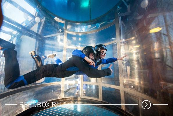 Парень и девушка летает в аэротрубе с инструктором